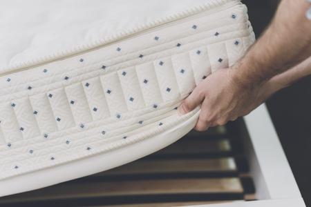 Foto de Close up. The man lifted the mattress to look at the bed frame - Imagen libre de derechos