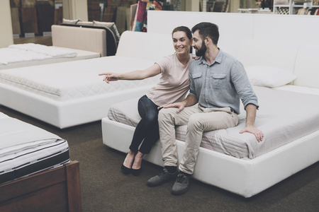 Photo for A couple is sitting on the bed, in a bed shop. They are happy - Royalty Free Image