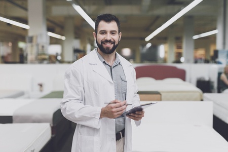 Foto de A male orthopedic pose against the background of a large store of beds. He holds tablet in his hands and looks at him. - Imagen libre de derechos
