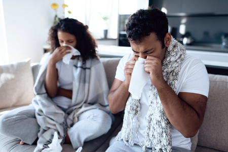Foto de Black man and woman are sitting on the couch. They catch a cold and blow their nose in paper napkins. - Imagen libre de derechos