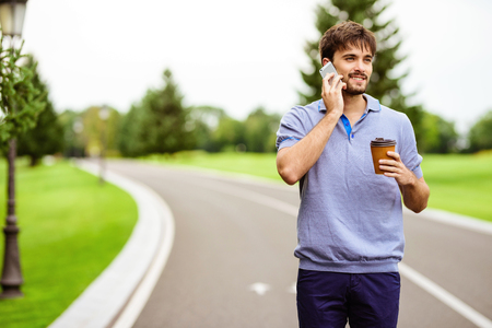 Photo for A man is driving through the park on a gyroboard. He is talking on the phone and is holding a glass of coffee - Royalty Free Image