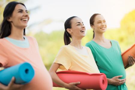 Foto de Three pregnant girls posing in a park with yoga mats in hand. They smile and have fun - Imagen libre de derechos