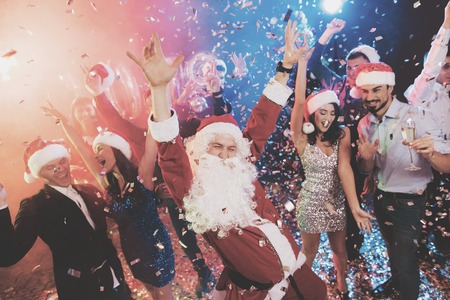 Foto für A man dressed as Santa Claus has fun at a New Year party. Together with him have fun friends. - Lizenzfreies Bild