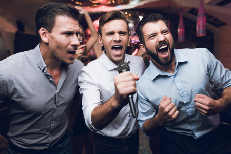 Photo for Three men sing at a karaoke club. Young people have fun in a nightclub. They are very cheerful and they smile. - Royalty Free Image