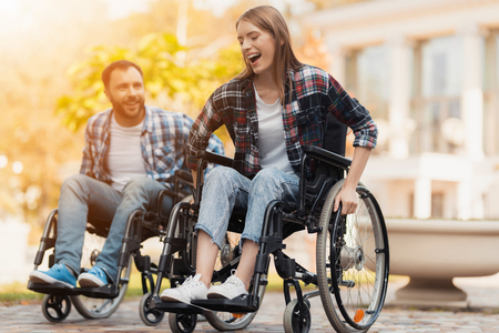 Foto de A man and a woman on wheelchairs ride around the park. They arranged a race in wheelchairs. - Imagen libre de derechos
