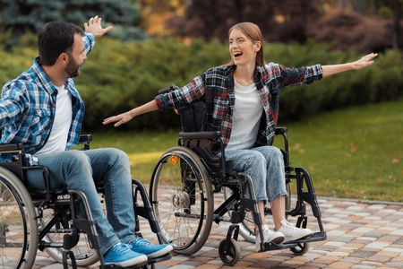 Foto de A man and a woman on wheelchairs ride around the park. They put their hands to one side and fooled around. - Imagen libre de derechos