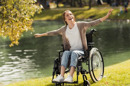 Foto de A woman in a wheelchair sits on the shore of a lake. She spread her arms out and laughed. - Imagen libre de derechos