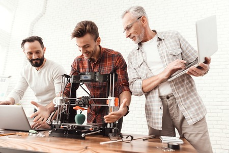Photo pour Two men set up a 3d printer, an elderly man holds a laptop in his hands and watches the process. - image libre de droit