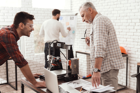 Foto de Three men set up a self-made 3d printer to print the form. They check the 3d model on the laptop. - Imagen libre de derechos