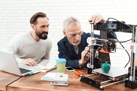 Photo for Two engineers print the details on the 3d printer. An elderly man controls the process. - Royalty Free Image