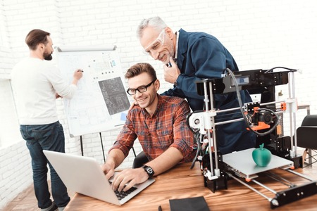 Photo for Three scientists are involved in setting up and developing 3D printers. An elderly man controls the work of his team. - Royalty Free Image