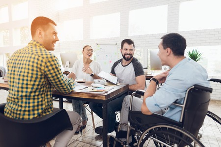 Foto de A man in a wheelchair communicates cheerfully with employees of the office during a business meeting. - Imagen libre de derechos