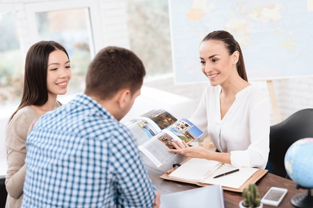 Foto per A young man and a woman came to the travel agency. - Immagine Royalty Free