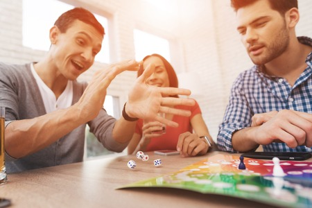Photo pour Young people play a board game using a dice and chips. - image libre de droit