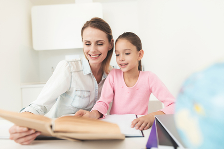 Photo for Mom helps my daughter do her homework in the kitchen. - Royalty Free Image