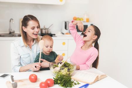 Foto de Mom and daughter have fun while preparing a salad. They are in a bright kitchen. - Imagen libre de derechos