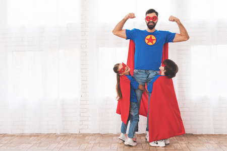 Foto de Father with children in red and blue suits of superheroes. They in masks and in raincoats. - Imagen libre de derechos