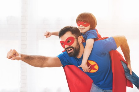 Photo for Father and son in the red and blue suits of superheroes. On their faces are masks and they are in raincoats. - Royalty Free Image