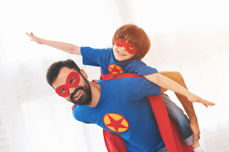 Foto de Father and son in the red and blue suits of superheroes. On their faces are masks and they are in raincoats. - Imagen libre de derechos