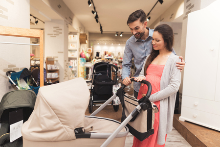 Photo pour A pregnant woman together with a man choose a baby carriage. - image libre de droit