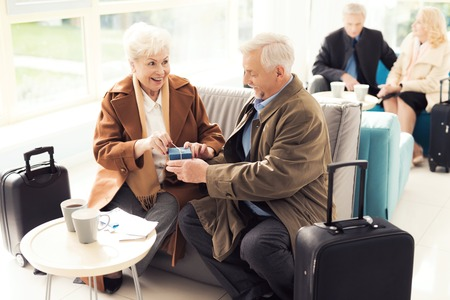 Photo for Elderly couple in the airport lounge. An elderly man makes an unexpected gift to an elderly woman. - Royalty Free Image