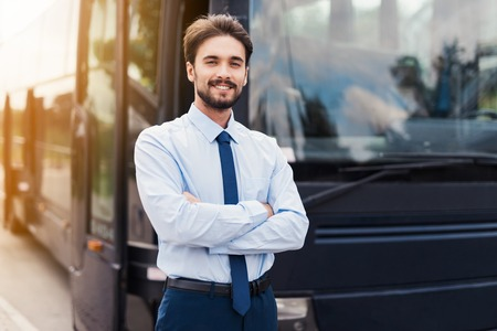 Photo for A male driver smiling and posing against a black tourist bus. Behind the back is a modern black tourist bus. - Royalty Free Image