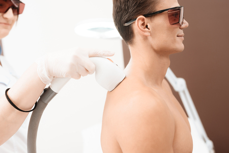 Photo pour The man came to procedure of laser hair removal. The doctor treats his shoulders, neck and back with a special apparatus - image libre de droit