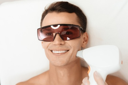 Photo pour The doctor treats the face of a man with a modern laser epilator. The man lies and smiles. - image libre de droit