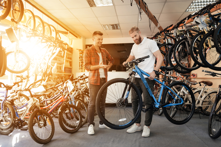 Foto de A seller at a bicycle store helps a young buyer choose a new mountain bike. - Imagen libre de derechos