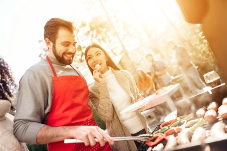 Photo for A man with girls fries sausages and vegetables on a barbecue. - Royalty Free Image