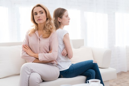 Photo for A woman and a girl are sitting on the sofa back to back. - Royalty Free Image