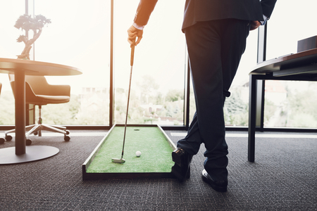 Photo pour Close up. A man in a business suit playing golf in the office. He is playing on a green mat. - image libre de droit