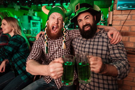 Foto de Two men in carnival caps celebrate St. Patricks Day. - Imagen libre de derechos