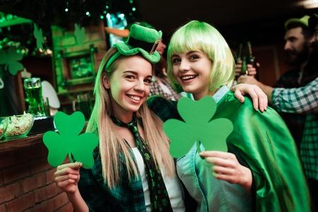Foto de Two girls in a wig and a cap are photographed in a bar. - Imagen libre de derechos