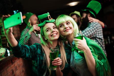 Foto de Two girls in a wig and hat make selfi at the bar. - Imagen libre de derechos