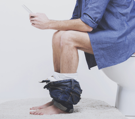 Photo pour Businessman is working with digital tablet while sitting on the toilet. - image libre de droit