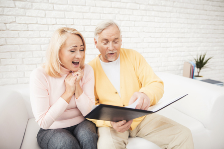 Photo for A man in a yellow cardigan and a woman in a pink sweater are sitting and reading documents in a black folder. They have a rapture on their face. They smile happily. - Royalty Free Image