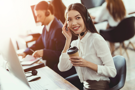 Foto de The Asian girl answers questions from clients in the call center. People from different nationalities work there. They work with computers and headphones. - Imagen libre de derechos