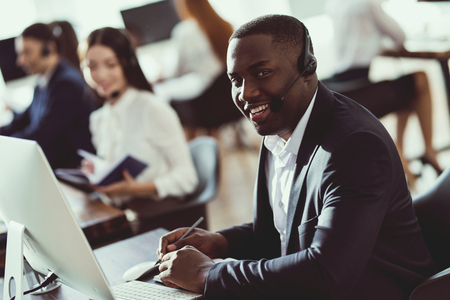 Foto de A black guy works in a call center. He has headphones on which they talk with customers. He is an operator and he answers questions. - Imagen libre de derechos