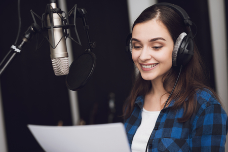 Photo for The girl in the recording studio sings a song. Her headphones are on her head. Next to her is a microphone. She emotionally sings the song. - Royalty Free Image