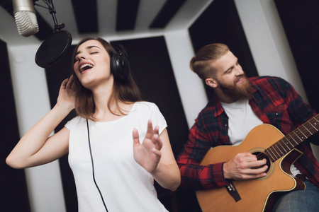 Photo for A girl and a guy sing a song to a guitar in a modern recording studio. The girl sings, and the guy plays the guitar. - Royalty Free Image