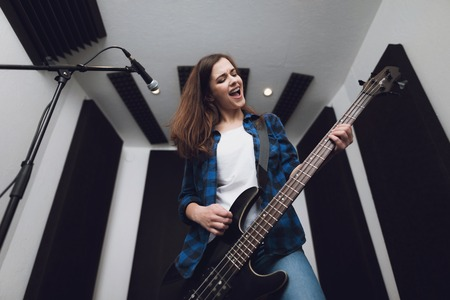 Photo for The girl is recording a song at a modern recording studio. She sings to the guitar. There is a microphone in front of her, she has an electric guitar in her hands. - Royalty Free Image