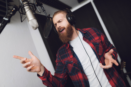 Photo for A man with a beard performs a song in a recording studio. He wears a plaid shirt. In front of him is a studio microphone. He sings enthusiastically. - Royalty Free Image