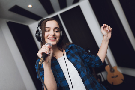 Photo for The girl sings her song in a modern recording studio. She sings the song very emotionally. In front of her is a studio microphone. - Royalty Free Image