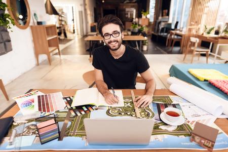 Photo pour Freelancer bearded man in t-shirt taking notes at laptop sitting at desk. - image libre de droit