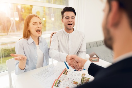 Foto de Young couple in a meeting with a realtor. A guy and a girl make a contract with a realtor about buying a property. A successful deal with a realtor. The client shakes hands with the realtor. - Imagen libre de derechos