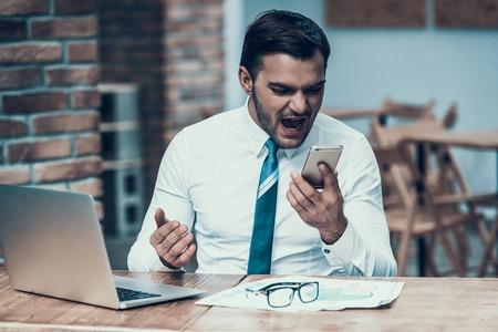Foto de Angry Indian businessman screaming at phone in office. Nervous breakdown. - Imagen libre de derechos