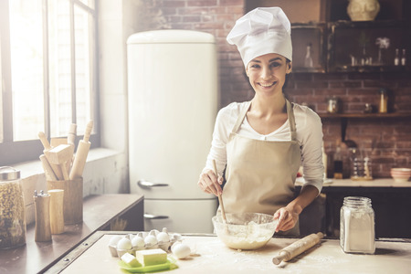Foto de Beautiful young woman in chef hat is mixing batter, looking at camera and smiling while baking in kitchen at home - Imagen libre de derechos