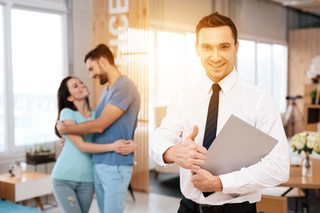 Foto de A manager in a tie poses on the camera. Near him are a guy and a girl who embrace. The man is showing his thumb. - Imagen libre de derechos
