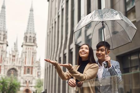 Photo pour Couple in love under umbrella in background of mall. Romantic concept. - image libre de droit